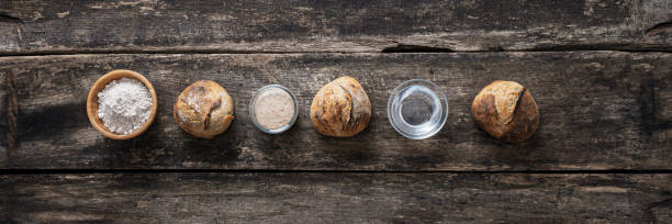 Home made bread buns and sourdough yeast placed on rustic wooden desk stock photo