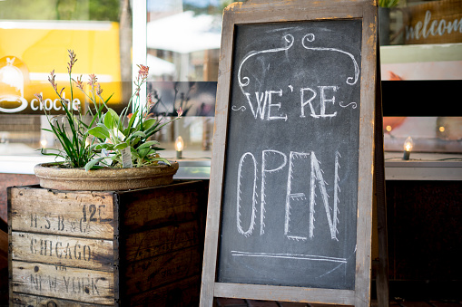 Home made farmhouse style We're open sign outside of a small business