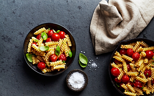 Home made fusilli pasta with cherry tomatoes and fresh basil leaves. Flat lay. Stone background
