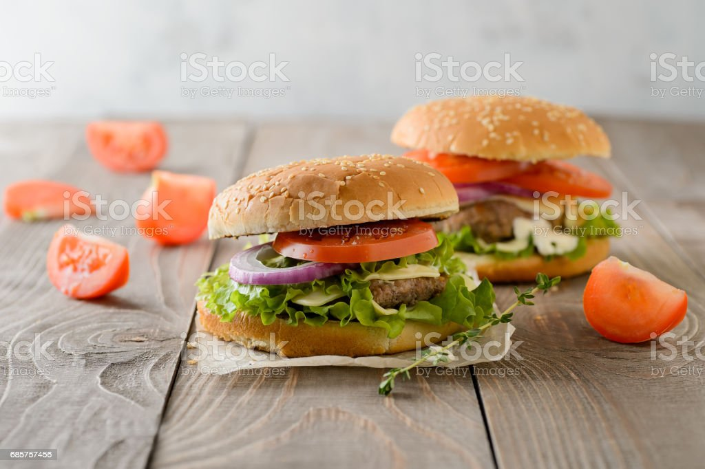 Home made hamburger with beef, onion, tomato, lettuce and cheese. Fresh burger closeup on wooden rustic table foto stock royalty-free