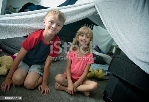 Siblings pose in front of home made blanket fort