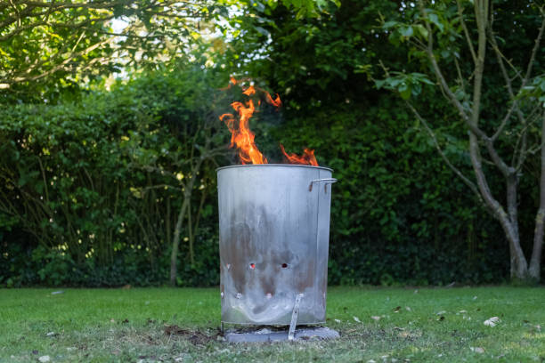 Home made metal garden incinerator seen burning household and garden waste in a back garden. The orange flames are seen reaching out of the metal barrel, with the heat reaching a very high temperature due to reflection from the inner metal surface. dumpster fire stock pictures, royalty-free photos & images