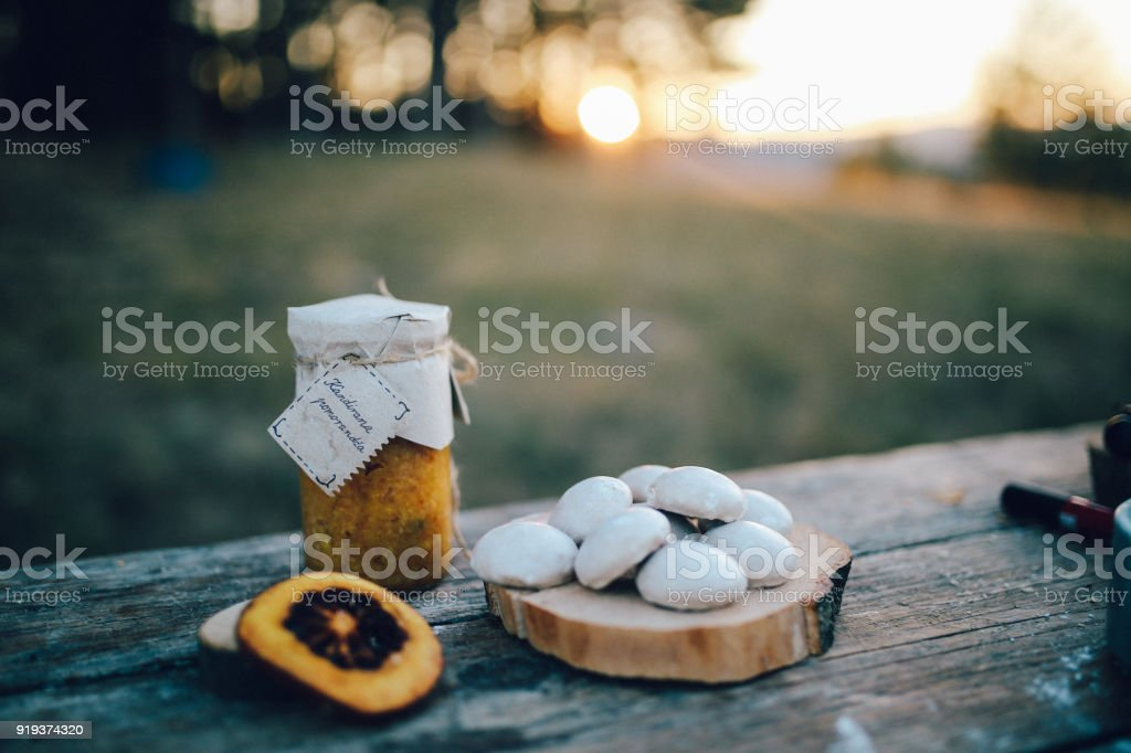 Home made paprika ajvar and some sweets on the rustic wooden table stock photo