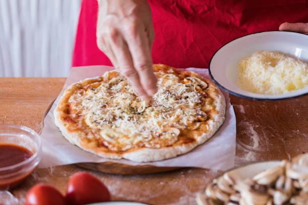 hausgemachte pizza, geriebener käse mit weißen pilzen, nahaufnahme - gebackene champignons stock-fotos und bilder