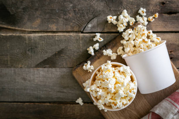 Home made pop corn in white cups on wood background