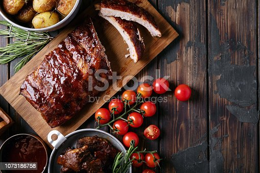 Home made pork and beef ribs, glazed with barbecue sauce served with baked rosemary potatoes, herbs and tomatoes, decorated with napkins over a rustic wooden background. Top View. Copy Space
