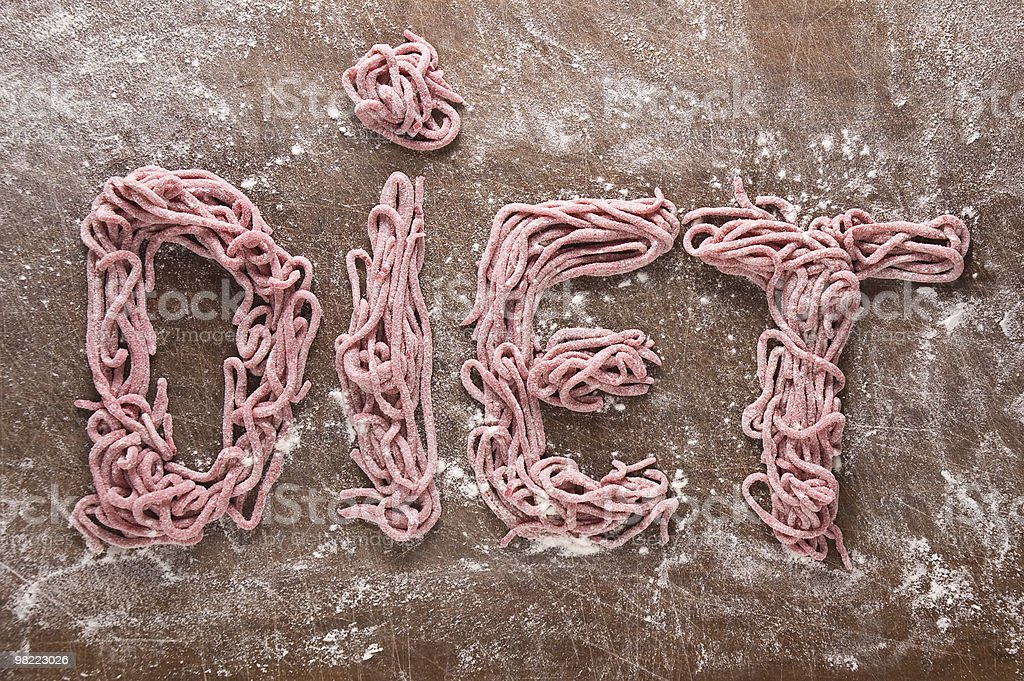 Home made red spaghetti forming the word DIET royalty-free stock photo