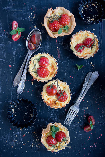 home made tarteletts with cherry tomatoes on black stock photo
