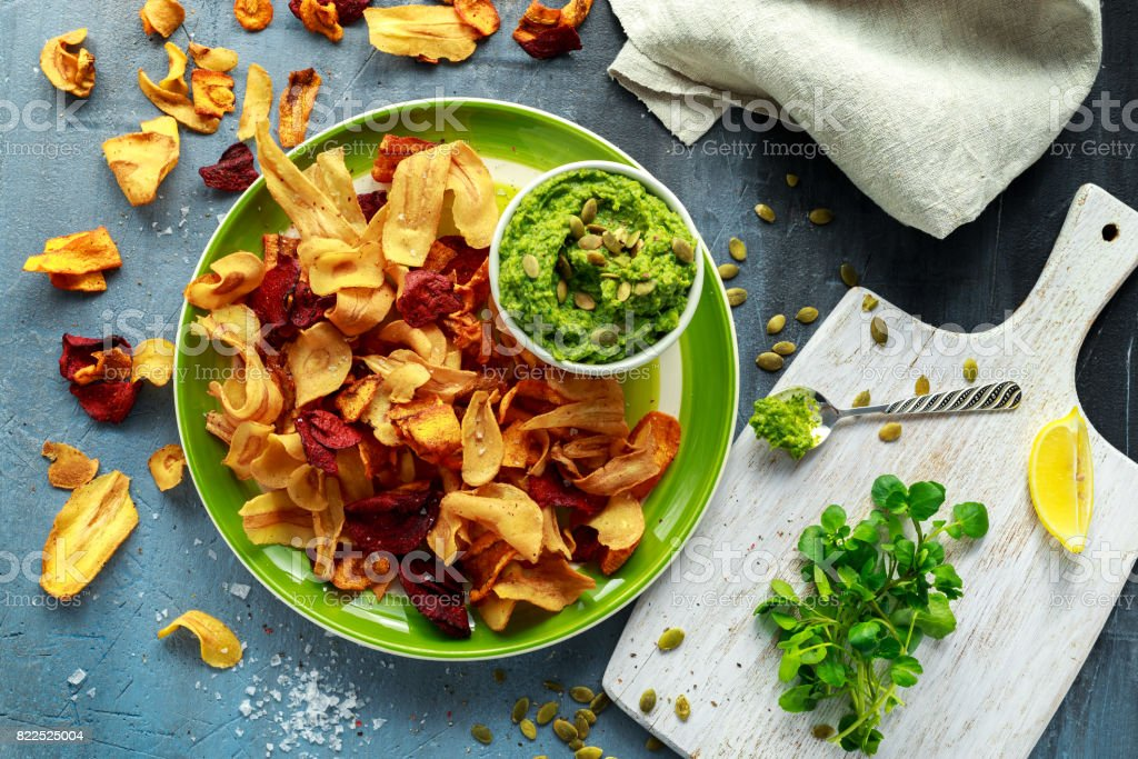 Home made vegetable crisps from carrots, parsnips and beetroot with watercress guacamole stock photo
