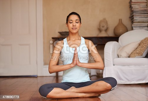 Full length shot of a young woman doing yoga in her living room
