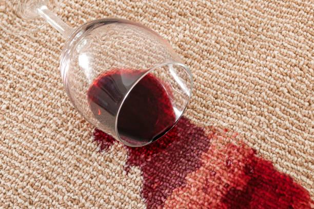 home ongeluk en binnenlandse ongeval concept met close up van een gemorste glas rode wijn op bruin tapijt - tapijt stockfoto's en -beelden
