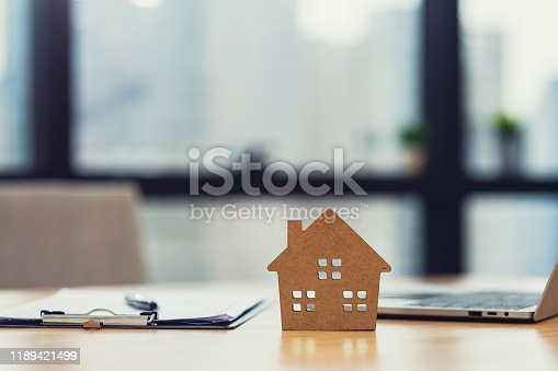 istock Home model put near Lease or Rental agreement document and laptop with copy space, real estate Business for buy 1189421499