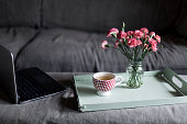 Home Moments - Cup of tea and flower bouquet on a tray with laptop beside