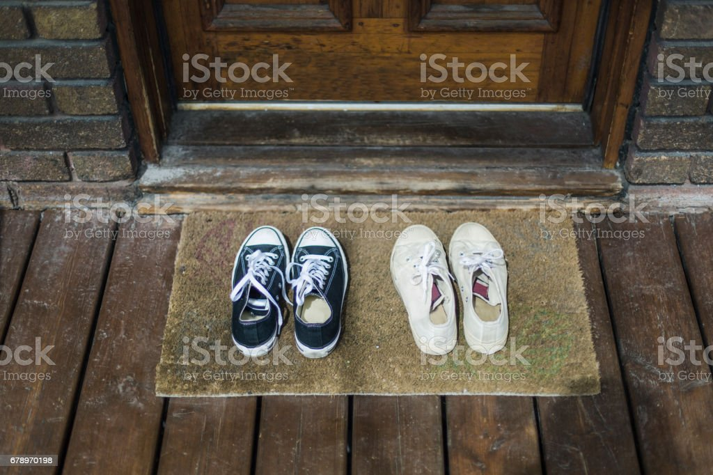 Home Moments - Two pair of black and whites sneakers shoes on a porch stock photo