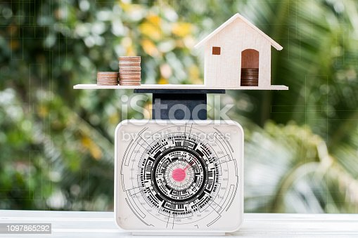 istock Home money coins on balance Weighing Scales with HUD IOT network  interface on wood green background. Concept of saving buy new home and mortgage investment real estate or cost of living house loan. 1097865292