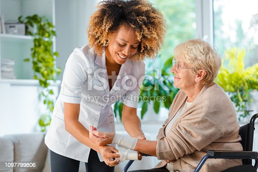 Afro american female home nurse bandaging the wrist to the senior woman. An elderly lady sitting in a wheelchair.