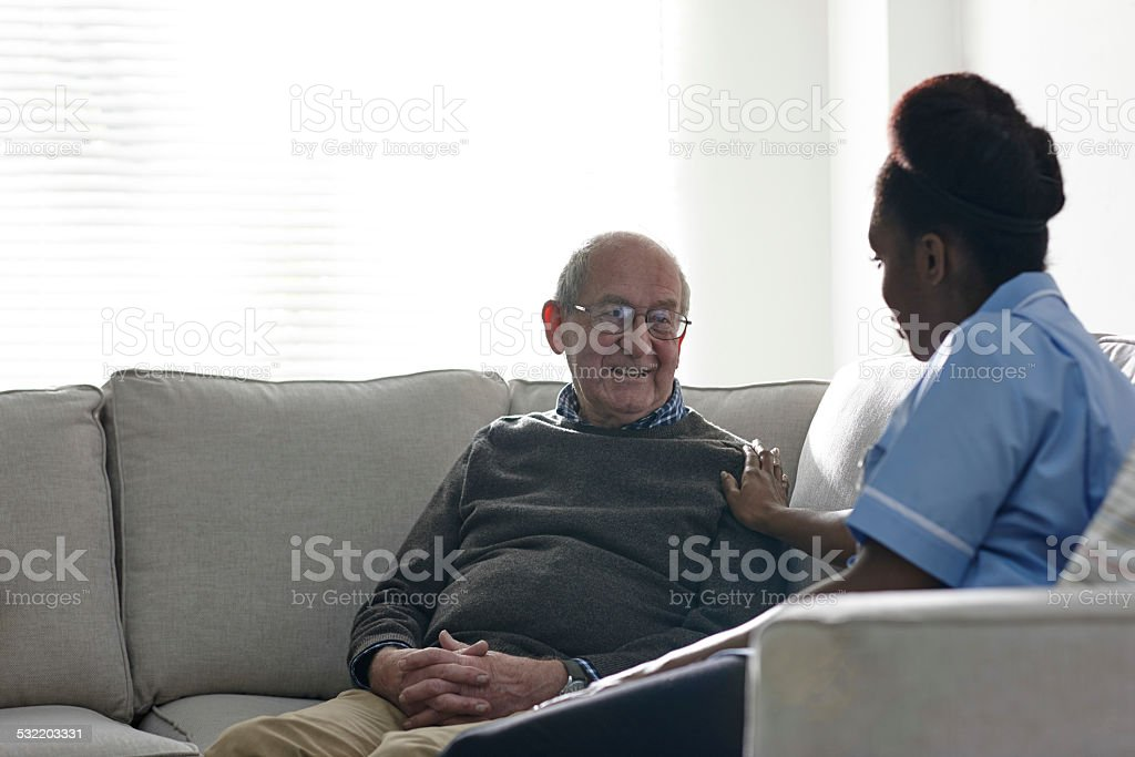 Home nurse taking care of senior man at home stock photo