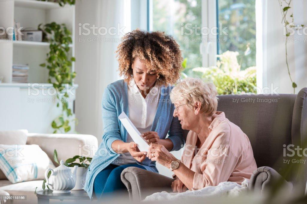 Home nurse taking care of senior woman stock photo