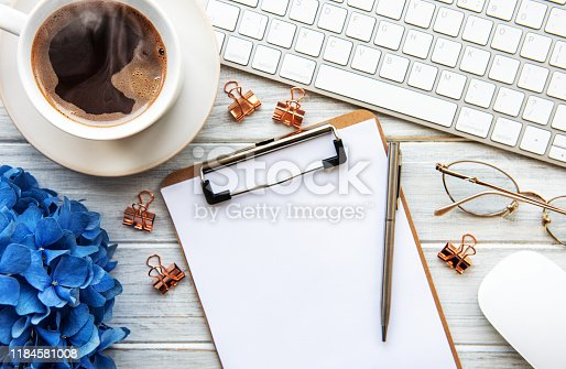Home office desk workspace with blank paper clipboard, blue hydrangea flower bouquet,  cup of coffee and keyboard  on white wooden background. Flatlay, top view.