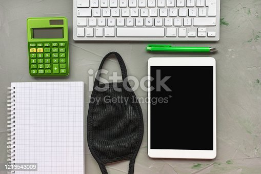 Man home office background. Mask, keyboard, tablet and notebook on gray. Coronavirus outbreak, quarantine work at home and tax return time concept. Mock up, top view, flat lay