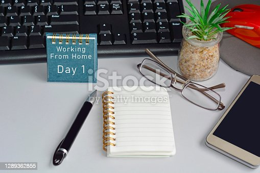 Home office desk with desktop, accessories and text written on blue note. Work from home concept