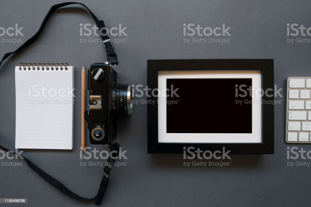 Home office desk with note pad, keyboard, pencil, photo camera and...