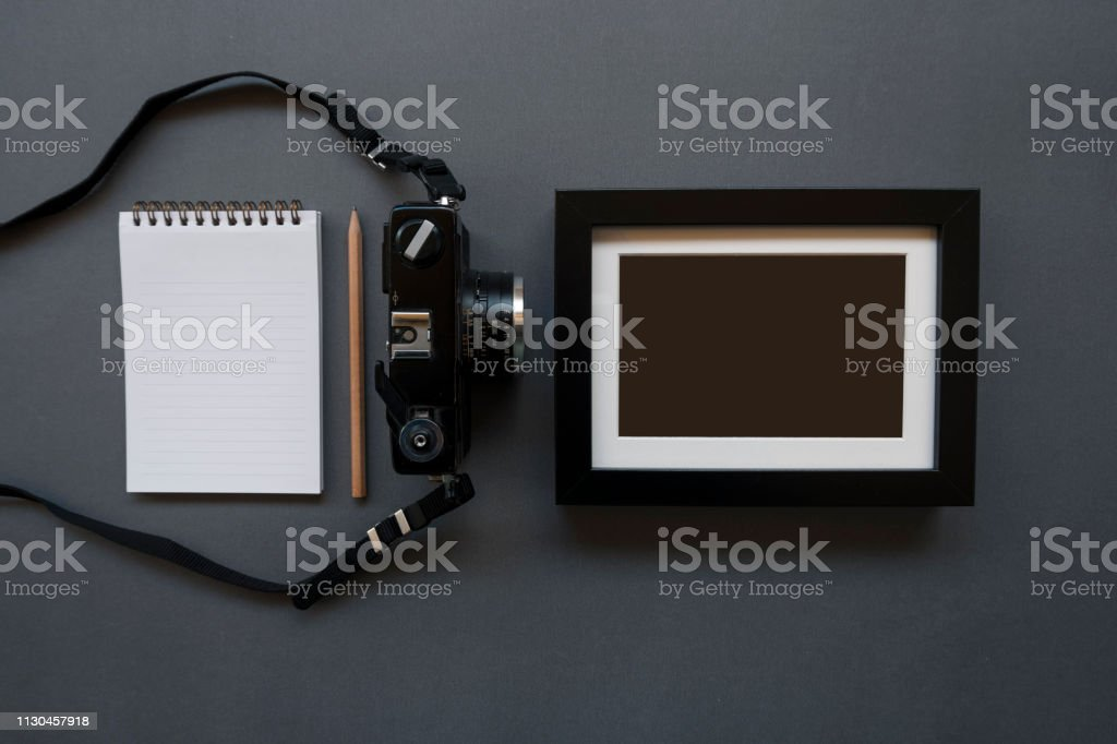 Home office desk with note pad, pencil, photo camera and frame