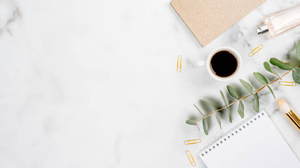 Home office desk with paper notepad, cup of coffee, glasses, office supplies and eucalyptus on white marble background. Flat lay, top view, copy space. Feminine workspace concept