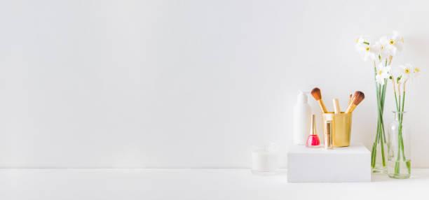 home office, interior for bloggers workplace with white daffodils in a vase, cosmetic set - prodotto per l'igiene personale foto e immagini stock