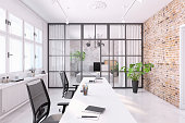 Modern home office interior, open plan studio with desks and office chairs. brick wall. white polished floor. vintage sliding still door. daylight scene with large windows. render