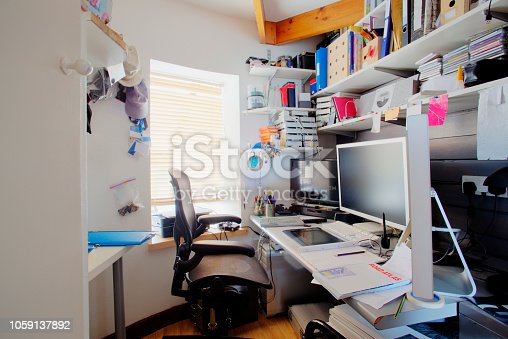 A shot of a messy desk in a home office, the room is small and cluttered, on the desk is three computer monitors and office supplies.