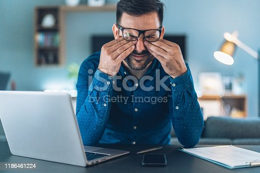 Tired young businessman working at home using lap top and looking Anxious
