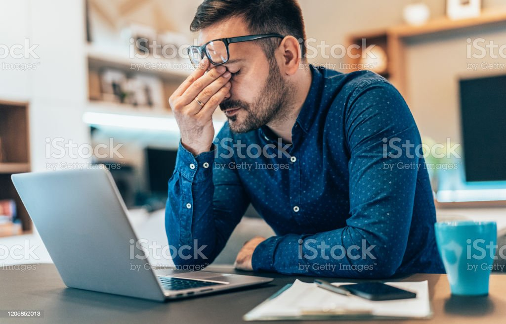 Home office Tired young businessman working at home using lap top and looking Anxious 30-39 Years Stock Photo
