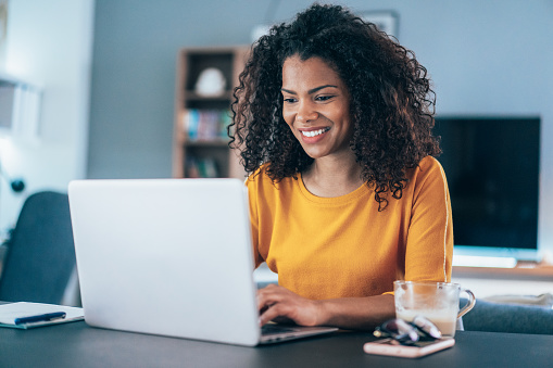 Young modern woman working from home, using laptop