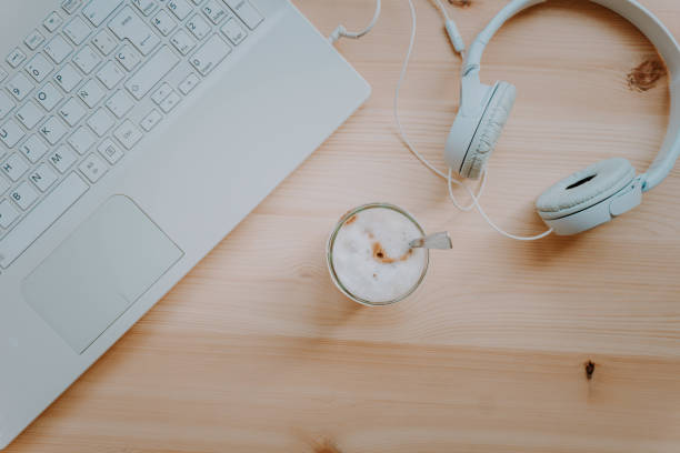 Home office. Quiet workspace with coffee, laptop and headphones. Work away. Relax and disconnection moment with chill music. Top view. stock photo