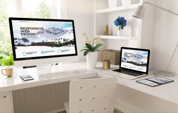 home office set up with responsive snow mountain website stock photo