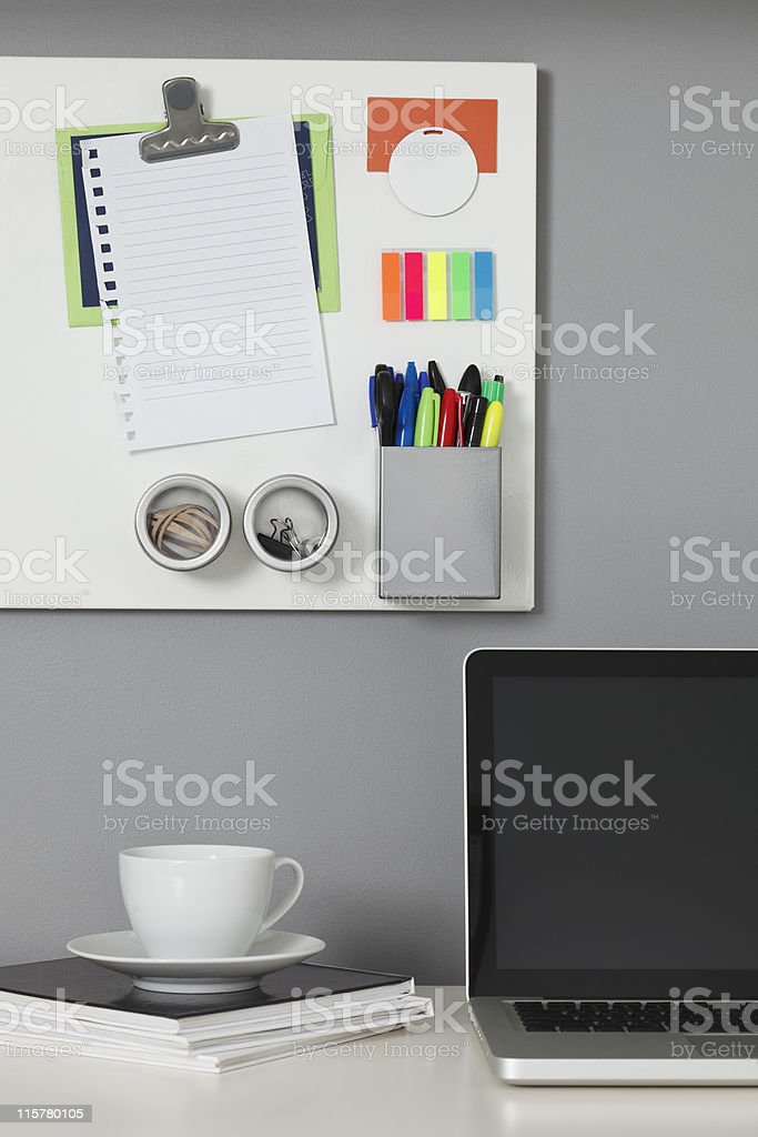 Home office with coffee, laptop, and memo board royalty-free stock photo