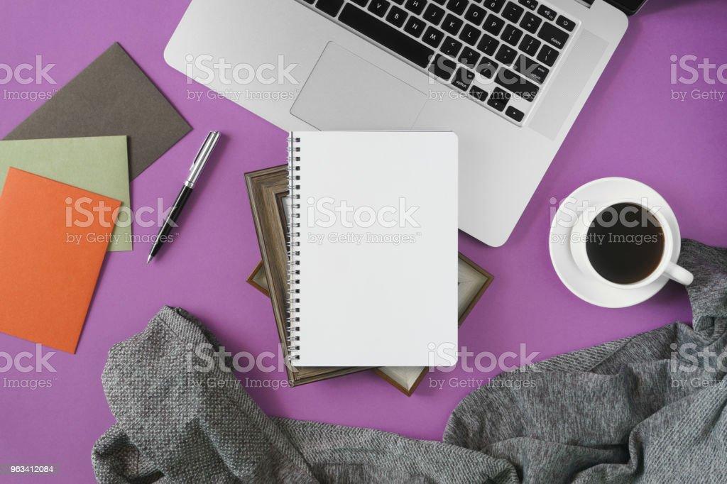 Domowe miejsce do pracy w biurze na fioletowym tle. - Zbiór zdjęć royalty-free (Biuro)