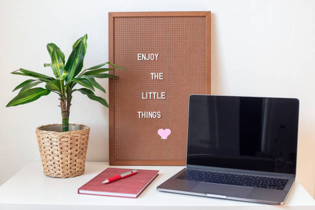 Home office workplace in scandinavian style, home interior with white table, laptop, green palm in a pot, pegboard with the inspiring phrase,  notebook, minimalistic concept, horizontal stock photo