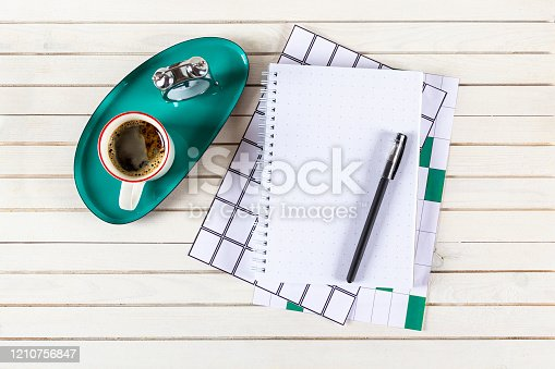 604021340 istock photo Home office workspace mockup with notebook, pen, cup of coffee, alarm clock and accessories on white wood desk background. Top view with copy space, flat lay. 1210756847
