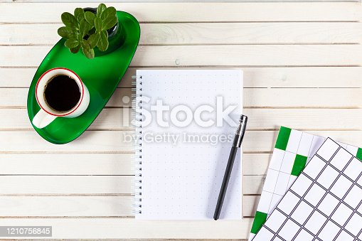 604021340 istock photo Home office workspace mockup with notebook, pen, cup of coffee,  plant potted on green tray and accessories on white wood desk background. Top view with copy space, flat lay. 1210756845