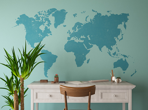 istock Home Office Workspace with Blue Wall and World Map 1204221781
