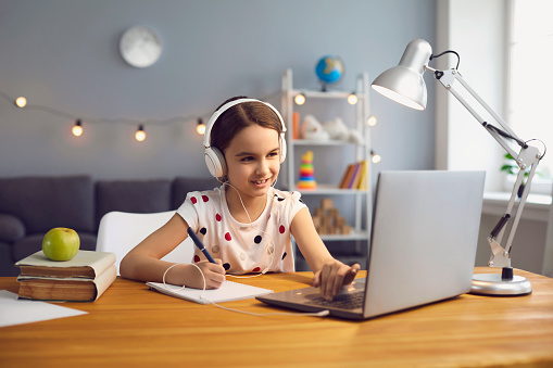Home schooling concept. Hardworking little girl in headset watching online lesson on laptop, taking notes into her copybook indoors