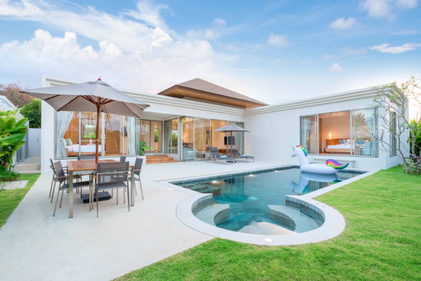 home or house  Exterior design showing tropical pool villa with greenery garden, sun bed, umbrella, pool towels and colorful floating unicorn home or house  Exterior design showing tropical pool villa with greenery garden, sun bed, umbrella, pool towels and colorful floating unicorn swimming pool stock pictures, royalty-free photos & images