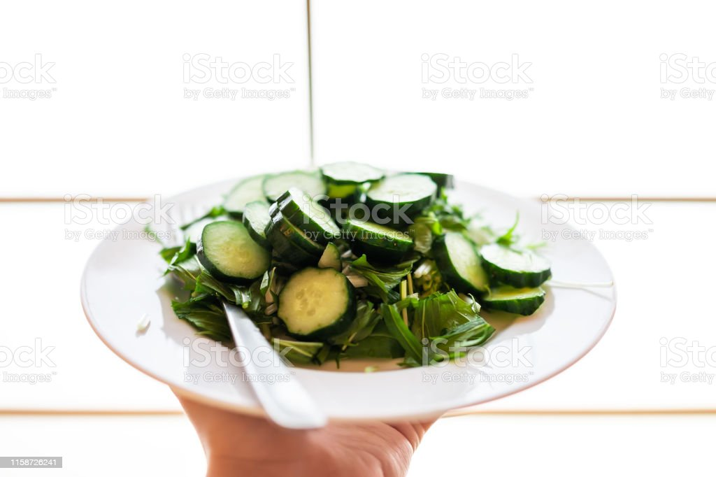 Home or restaurant with hand holding green salad dish closeup with...