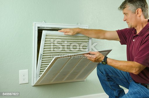 931591820 istock photo Home owner replacing air filter on air conditioner 545567622