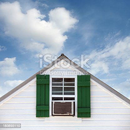 close up shot of window from a old house over cloudy sky.