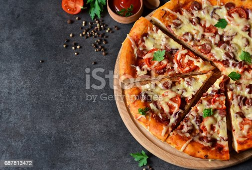 istock Home pizza with salami, tomato and cheese on a black background 687813472