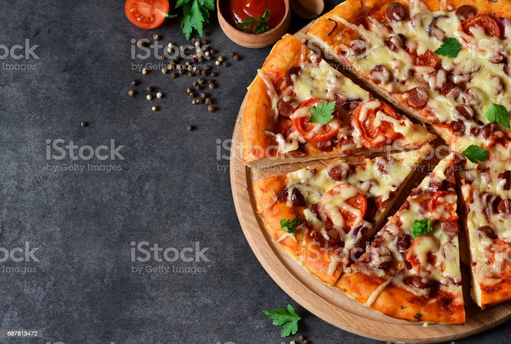 Home pizza with salami, tomato and cheese on a black background stock photo