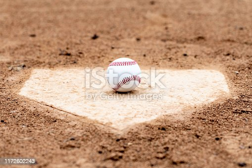 Baseball laying on a worn home plate or base